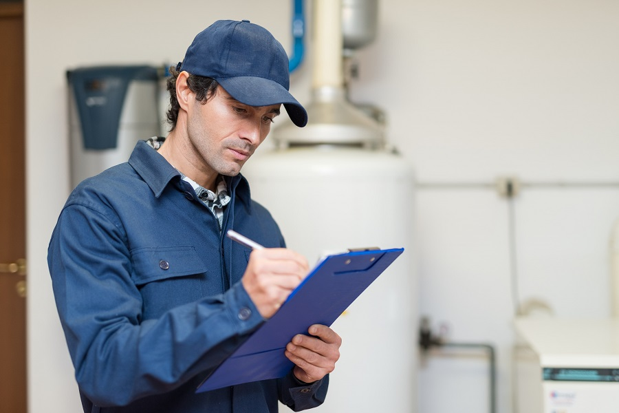 plumbing technician looking at clipboard